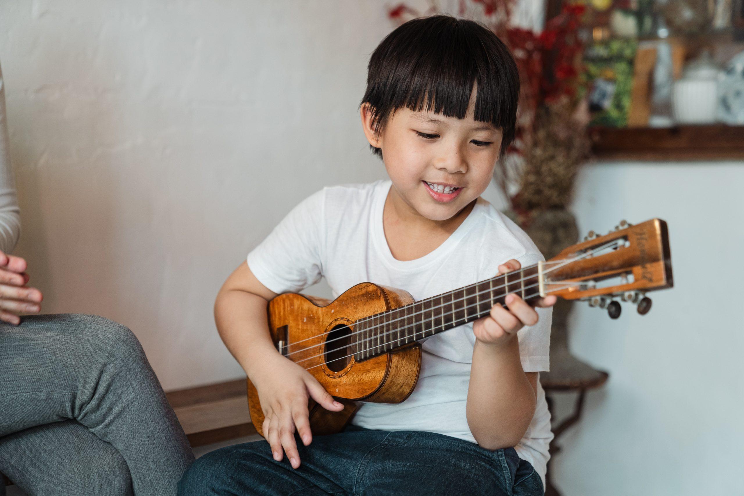 child playing ukulele making music