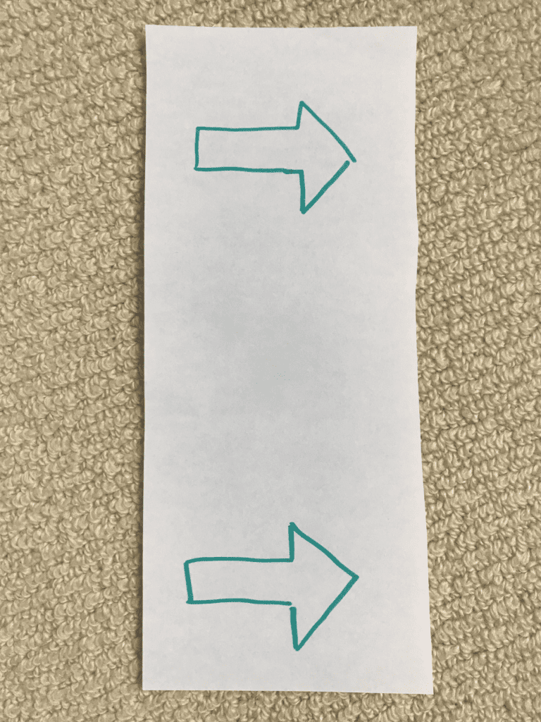 piece of paper with two arrows pointing right (one at top of paper, one at bottom)