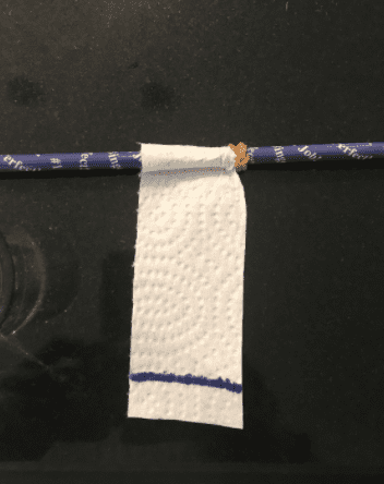 Small, vertical rectangle paper towel attached to a pencil with an elastic.